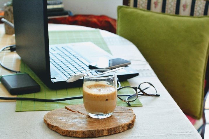 laptop, phone, glasses and coffee on home office table