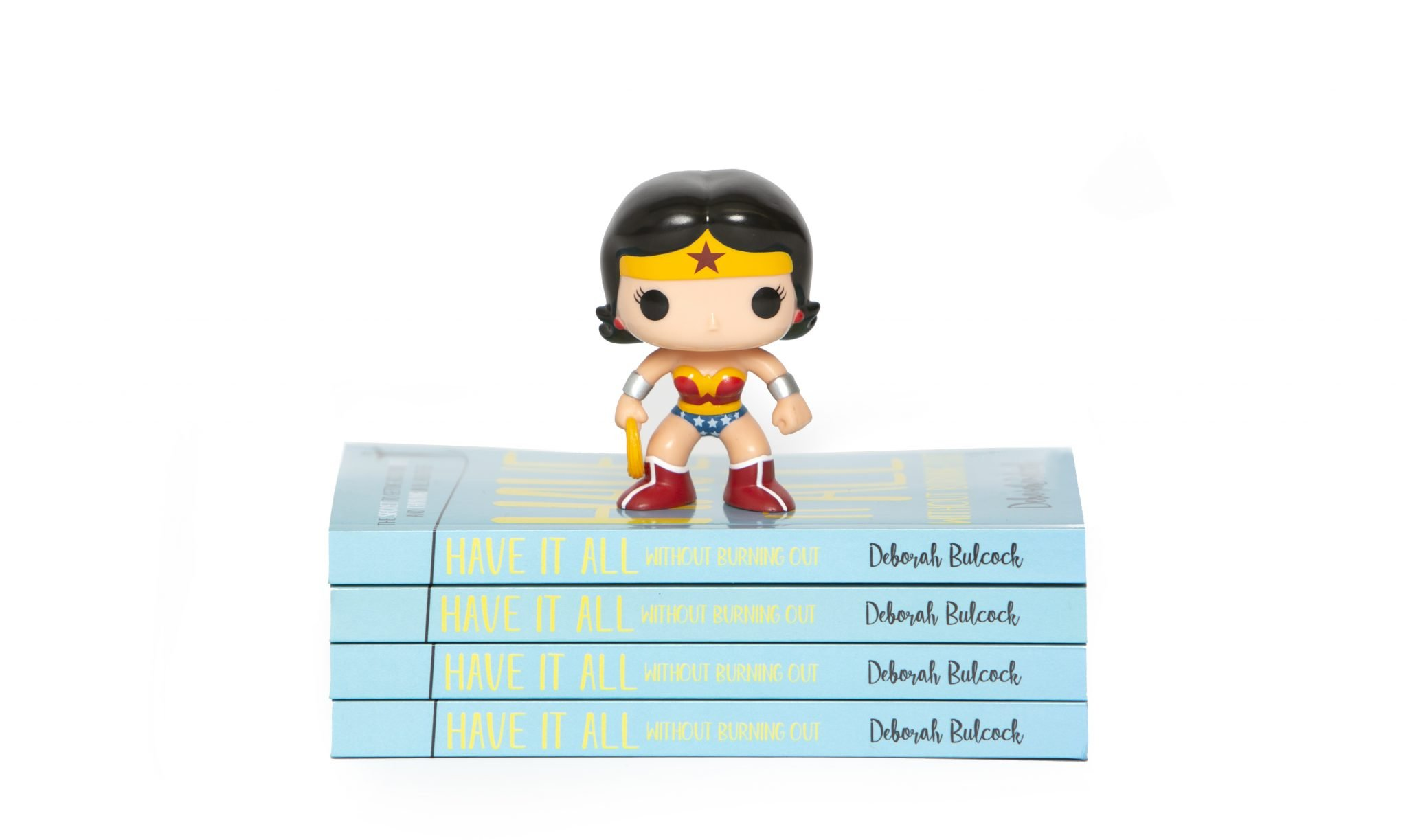 Wonder Woman action figure placed on top of the book 'Have It All Without Burning Out'