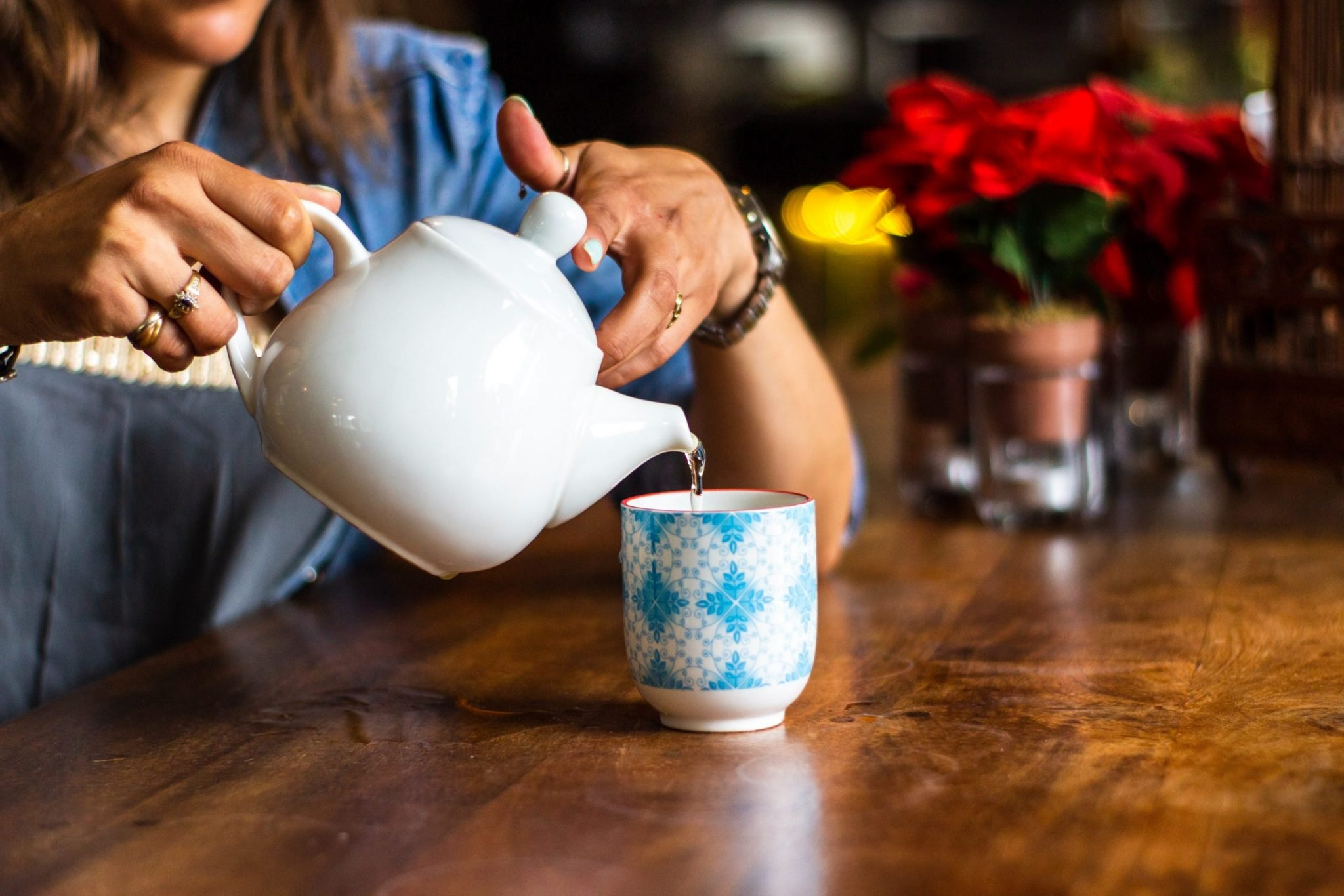 Woman pouring tea into cup from teapot - representing a restful break