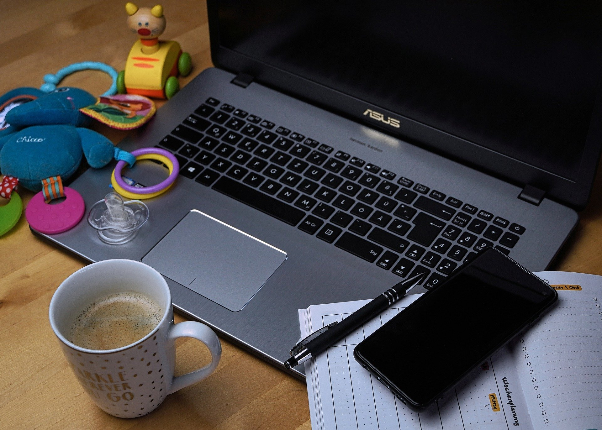 Computer, drink and children's toys - representing working from home with children during the pandemic